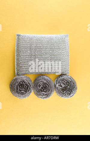 pattern of silver shiny new steel wool cleaning sponges with circles and squares on yellow backdrop. - Stock Photo