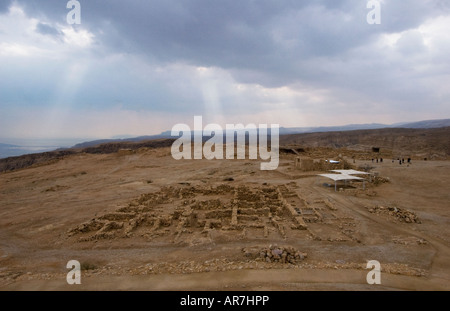 Masada plateau - view of the western palace. Sun rays filtering through the clouds on an unusually cloudy day - Stock Photo