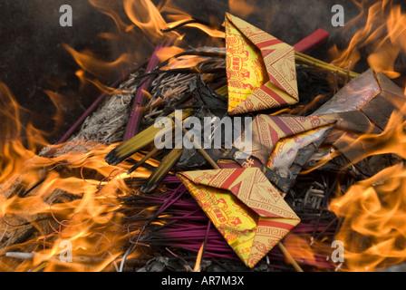 Burning of joss paper money, at the Lingyin Temple, Hangzhou, Zhejiang China - Stock Photo