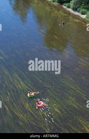 Man and woman in swimsuits and using inflatable rings drift downstream with the river's current on a sunny day in - Stock Photo