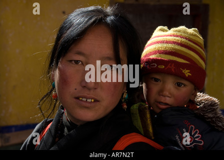 A horizontal photo of Tibetan lady pilgrim holding her baby on the steps of the Potala palace New Years day, Lhasa - Stock Photo