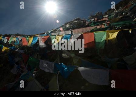 View of Prayer Flags taken into the sun on the pilgrims Kora at Ganden monastery Tibet - Stock Photo