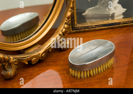 Dressing table with antique pewter brush, mirror, and frame - Stock Photo