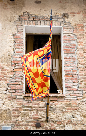 A stuffed teddy bear looks peeks out from a child s bedroom behind a contrade flag in Montepulciano Tuscany - Stock Photo