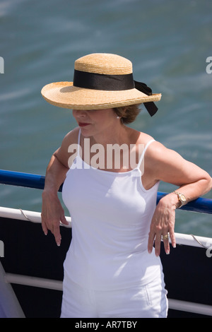 A woman wearing a straw hat relaxes against the railing of a ship on a warm and sunny day. - Stock Photo