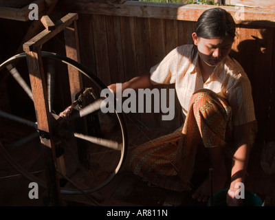 woman in the sunlight spinning her wheel weaving lotus threads into silk at Inle Lake in Myanmar - Stock Photo