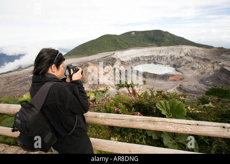 Costa Rica Poas Volcano National Park visitor taking picture of main crater and hot lake laguna caliente - Stock Photo
