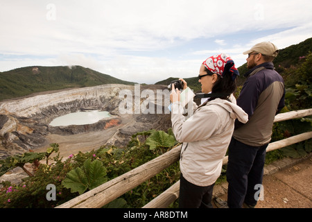 Costa Rica Poas Volcano National Park visitors taking picture of main crater and hot lake laguna caliente - Stock Photo