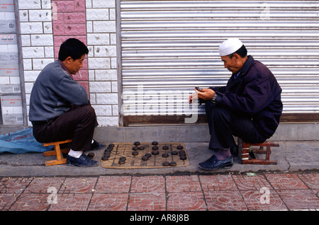 Chinese men playing Xiangqi also called Chinese chess which is a strategy board game in a sidewalk in the town of - Stock Photo