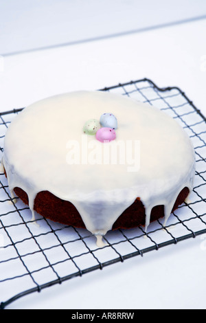 Home baked Easter cake with fondant icing and finished with sugar coated chocolate easter eggs served on baking - Stock Photo