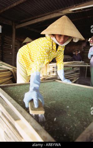 Woman Cleaning Fish Racks - Stock Photo