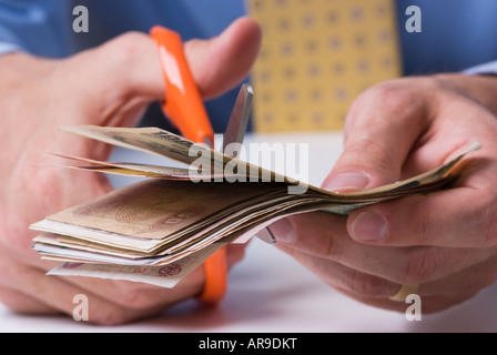 Close up shot of business man holding money cutting up bank notes with scissors - Stock Photo