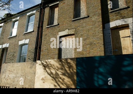 derelict boarded-up house in north london - Stock Photo