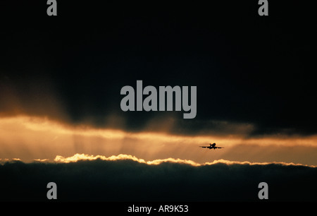 Boeing jet airliner flying in dark cloudy sky at sunset - Stock Photo