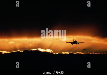 Airbus jet airliner flying at sunset sunburst - Stock Photo