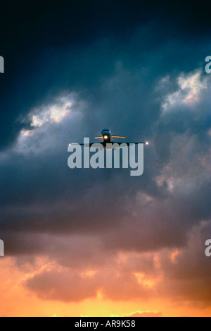 jet airliner with lights on approach to airport in a dark cloudy sky dusk - Stock Photo