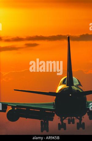 Boeing 747 jumbo jet airliner landing at sunset - Stock Photo
