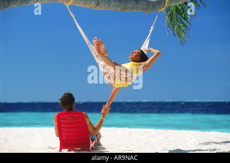 Couple chilling out in hammock and chair under palm tree and blue skies on white sandy beach on Fihalhohi Island - Stock Photo