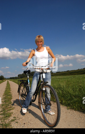 junge blonde Frau mit Fahrrad - young blonde woman with bike - Stock Photo
