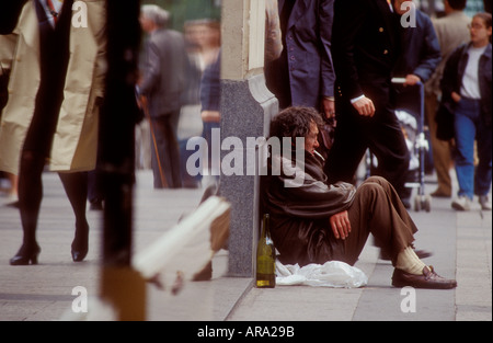 Homeless man sitting on busy shopping center city street smoking and drinking ignored by passers by - Stock Photo