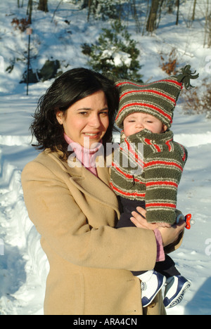 Hispanic mother and six (6) month old grandson pose outside in the snow.  Melrose Massachusetts, USA - Stock Photo