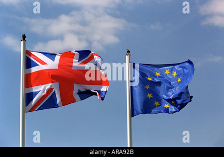 A United Kingdom flag flying next to a European Union flag - Stock Photo
