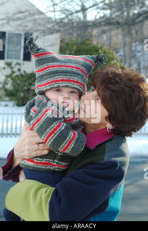 Grandmother and six (6) month old grandson pose outside in the snow.  Melrose Massachusetts, USA - Stock Photo