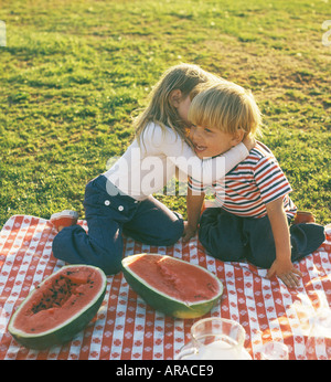 small boy and girl whispering on picnic - Stock Photo