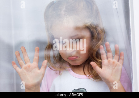 Sad young girl (5-7 years) with hands pressed against glass window looking out - Stock Photo