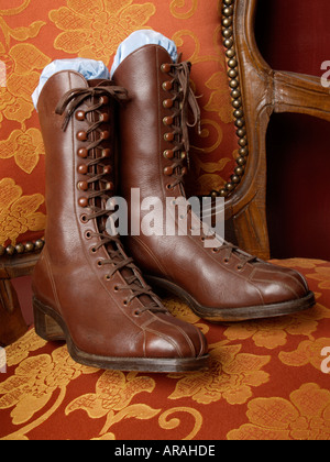 Pair of nostalgic old laced ladies boots shoes on antique chair - Stock Photo