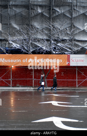 Pedestrians cross Eighth Avenue at Columbus Circle in a snow squall near the future Museum of Arts and Design in - Stock Photo