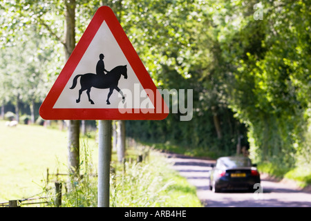 Car passes sign by roadside warning of accompanied horses or ponies Dorset UK - Stock Photo