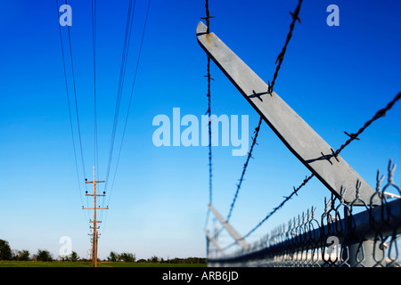 Telephone Wires and Barbed Wire Fence - Stock Photo