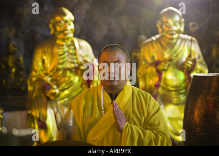 Buddhist monk drums and chants inside temple cave, Yangdang Mountains, Wenzhou, Zhejiang Province, China - Stock Photo