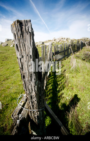 Worn down wooden fence along a grassy knoll with large boulders in the background - Stock Photo