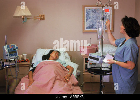 Female patient in hospital bed connected to IV with nurse in attention - Stock Photo