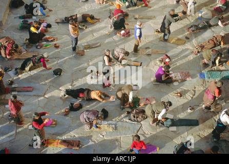 Buddhist pilgrims prostrating, Barkhor Jokhang Temple, Lhasa, Tibet, China - Stock Photo