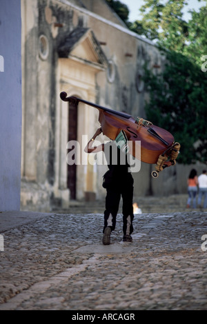 Musician carrying double bass along cobbled street to Plaza Mayor, Trinidad, Cuba, West Indies, Central America - Stock Photo