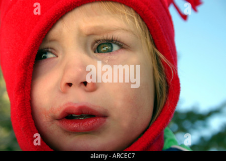 child crying with red hat winter - Stock Photo