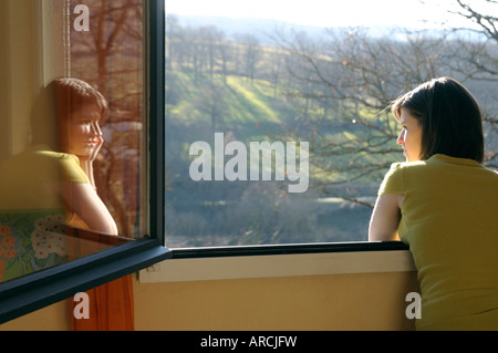 Young woman looking out of a window at a countryside view - reflected in the glass, rear view - Stock Photo