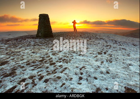 A lone hiker watches the sunset from the top of Mam Tor in Derbyshires Peak District - Stock Photo