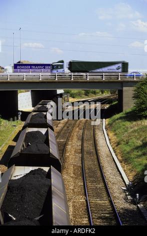 vehicles on motorway traveling on bridge over railway carriges full of coal leading to ferrybridge power station - Stock Photo