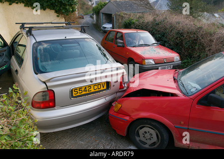Drink Drive collision on narrow country road between two cars red fiesta into back of parked silver Rover writing - Stock Photo
