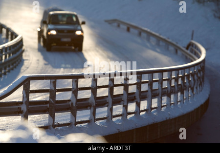 Metallic snowy road bridge railing and car driving on the road at Winter , Finland