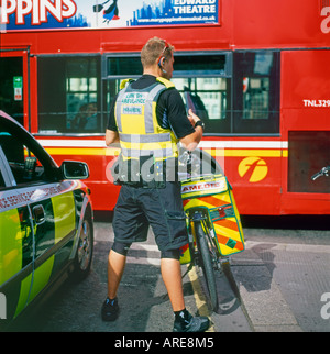 Paramedic from the London Ambulance Service on duty standing by his bicycle in London England UK  KATHY DEWITT - Stock Photo