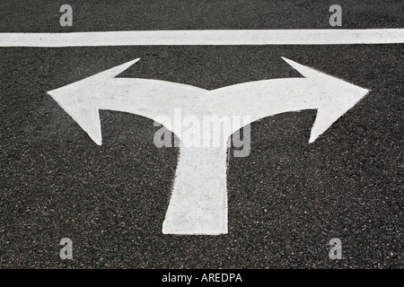 Dual directional arrows indicating must turn left or right painted on road pavement - Stock Photo