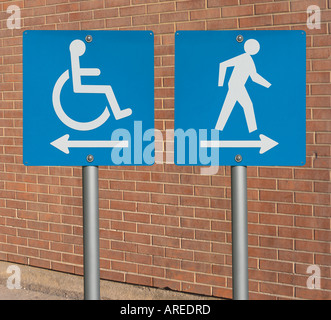Wheelchair sign with arrow pointing left beside sign with a person walking and with an arrow pointing right - Stock Photo