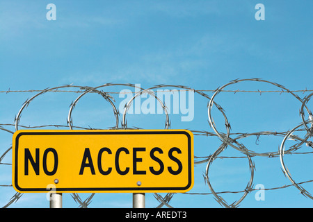 NO ACCESS warning sign in front of razor wire - Stock Photo