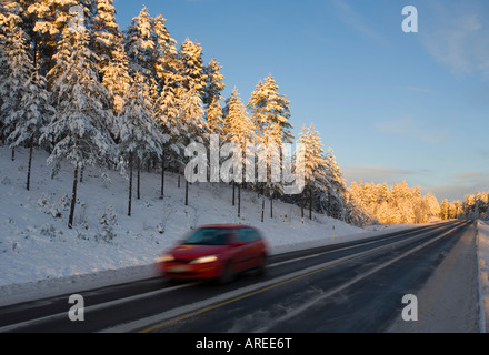 Car driving on Finnish highway at evening at Winter Finland - Stock Photo
