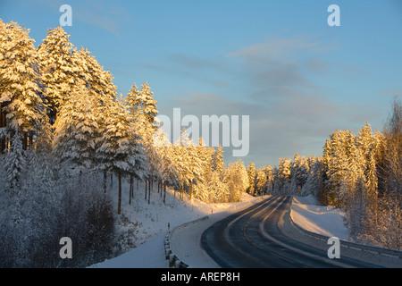 Empty Finnish highway ( valtatie 9 , Highway 9 , E63 ) at evening light at Winter Finland - Stock Photo